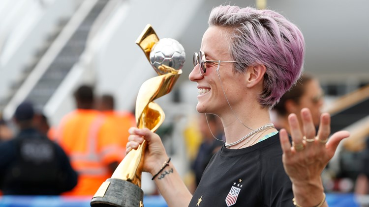Rapinoe with trophy US Returns Home Soccer