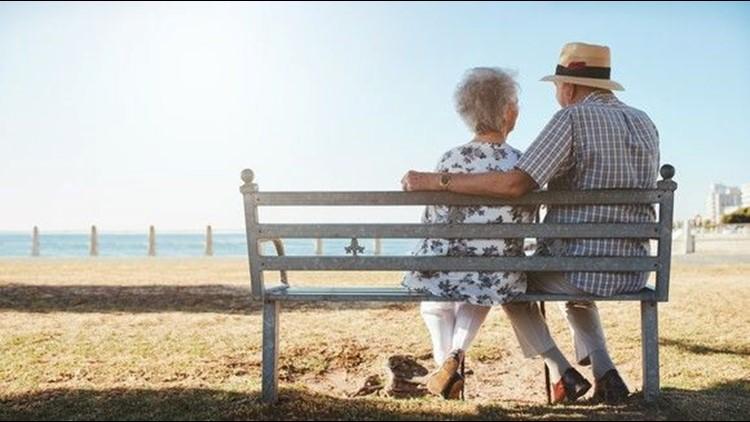 elderly-senior-couple-sitting-on-a-bench-on-the-beach_large.jpg