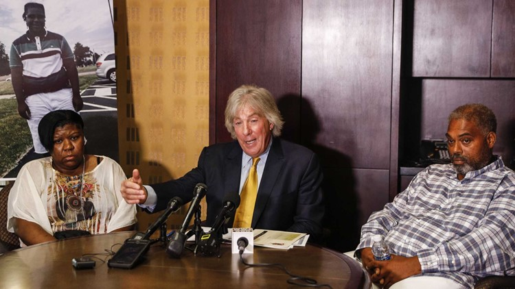 Monique Grimes, left, and John Grimes, right, with attorney Geoffrey Fieger, hold a news conference in August 2017 about the $50-million lawsuit against a Michigan State Police trooper who they say killed 15-year-old Damon Grimes.