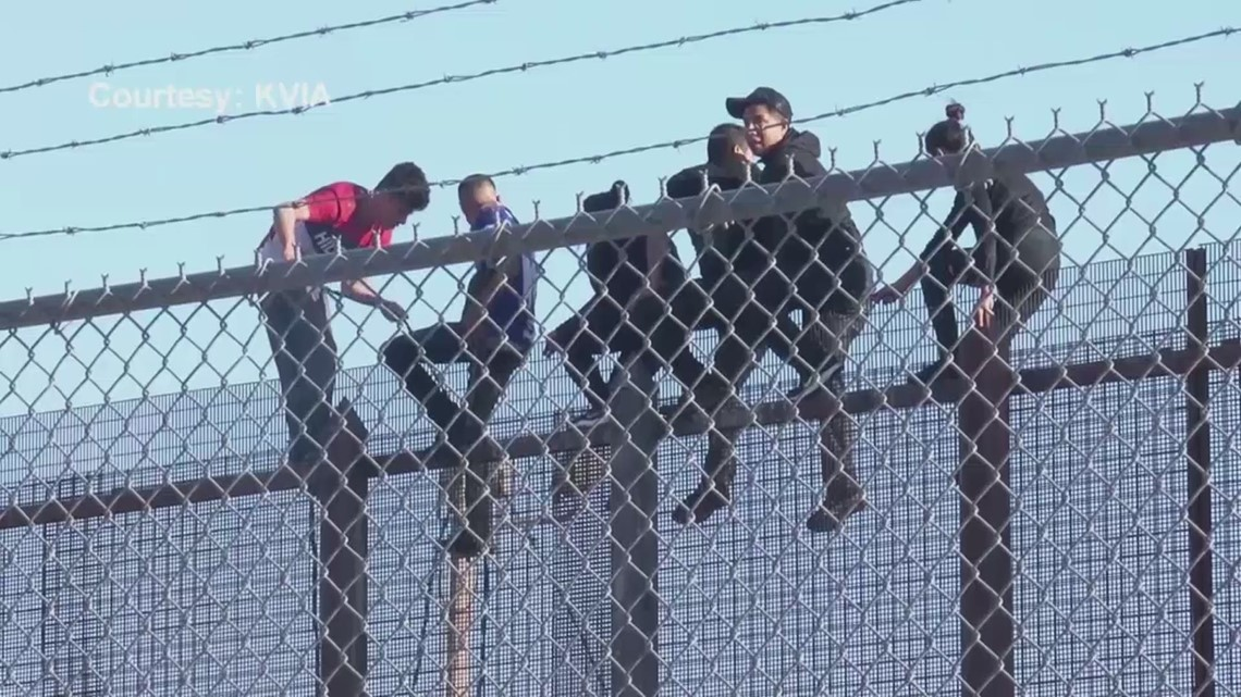 WATCH: Migrants use rope ladder to climb over border barrier