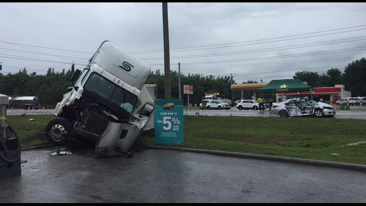 The big rig ended up on its side in a gas station parking lot. The driver of the car was killed.