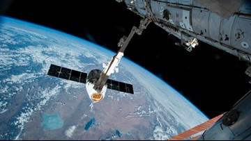Spacewalking astronauts adding parking spot to space station