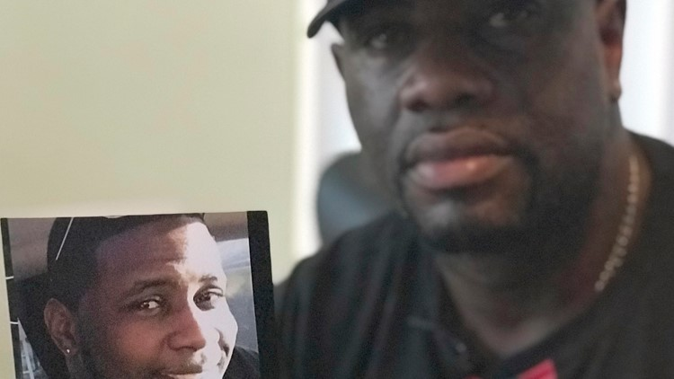 Markeis McGlockton's father holds up a photo of him